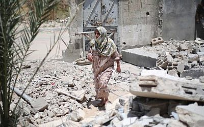 A Palestinian woman walks amid the rubble of buildings which were destroyed during the 50-day war between Israel and Hamas in the summer of 2014, in the village of Khuzaa, east of Khan Yunis, in the southern Gaza Strip, June 1, 2015. (AFP/SAID KHATIB)