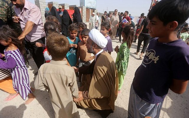 A representative of Iraq's Shiite spiritual leader talks with displaced Iraqi children who fled Ramadi, after it was seized by the Islamic State, at a makeshift camp for internally displaced persons in Ameriyat al-Fallujah, June 6, 2015. (AFP/Ahmad al-Rubaye)