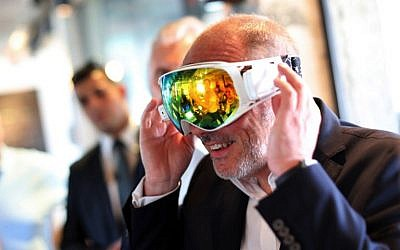 Orange CEO Stephane Richard tries on goggles during a visit at the French telecom lab in Tel Aviv, on June 11, 2015. (AFP/DANIEL BAR-ON)