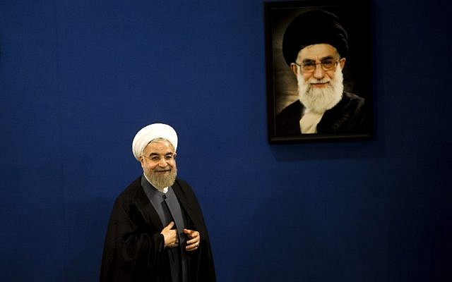 Iranian President Hassan Rouhani stands next to a portrait of supreme leader Ayatollah Ali Khamenei as he leaves at the end of a press conference in Tehran on June 13, 2015. (AFP Photo/Behrouz Mehri)