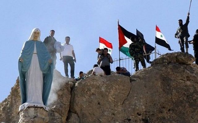 Members of the Syrian National Defense Forces (NDF) stand behind a statue of Virgin Mary perched on the cliffs overlooking the ancient Christian town of Maalula, 56 kilometers northeast of the Syrian capital Damascus, on June 13, 2015 after the statue was restored to its original place. (AFP PHOTO / LOUAI BESHARA)