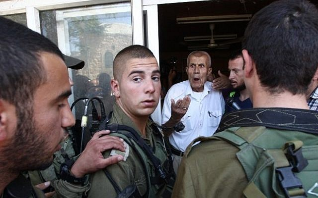 Israeli soldiers react as an elderly Palestinian storekeeper tries to open his shop following a decision by the IDF to allow the reopening next week of dozens of shops in Hebron, which have been closed for almost 15 years, on June 15, 2015. (AFP/Hazem Bader)