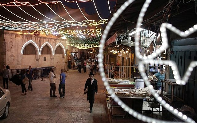 A picture taken on June 16, 2015 shows an ultra-Orthodox Jewish man (C) walking as fairy lights decorate a shop near the entrance of the Al-Aqsa mosque compound on the Temple Mount, in the old city of Jerusalem, as Muslims around the world prepare for the announcement of the fasting month of Ramadan. (AFP PHOTO/AHMAD GHARABLI)