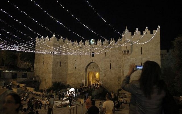 People walk under lights decorating Damascus Gate outside the Old City of Jerusalem on June 16, 2015, as Muslims around the world prepare for the announcement of the fasting month of Ramadan. (AFP PHOTO/AHMAD GHARABLI)