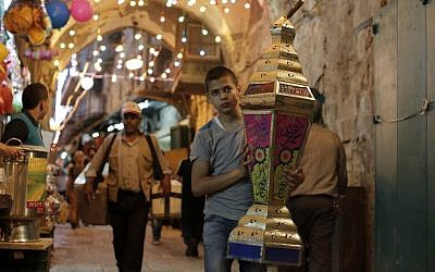Illustrative. A Palestinian boy carries a lantern past shops in the Old City of Jerusalem on June 16, 2015.(AFP PHOTO/AHMAD GHARABLI)