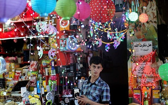 """A Palestinian vendor displays traditional lanterns known in Arabic as """"Fanous"""" sold during the Muslim holy month of Ramadan at a market in Gaza City, on June 17, 2015, as the faithful prepare to start fasting. (AFP PHOTO/MAHMUD HAMS)"""
