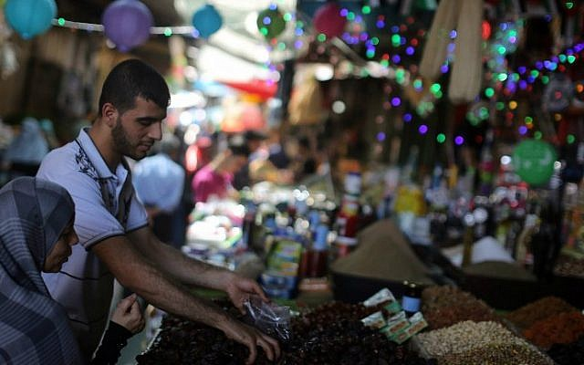 A Palestinian woman buys dates at a market in Gaza City as the faithful prepare for the start of the Muslim holy fasting month of Ramadan on June 17, 2015. (AFP PHOTO/MAHMUD HAMS)