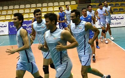 A file picture taken on July 8, 2014, shows Iran's volleyball national team players warming up during a training session at Azadi sports hall in Tehran.  (AFP PHOTO / BEHROUZ MEHRI)