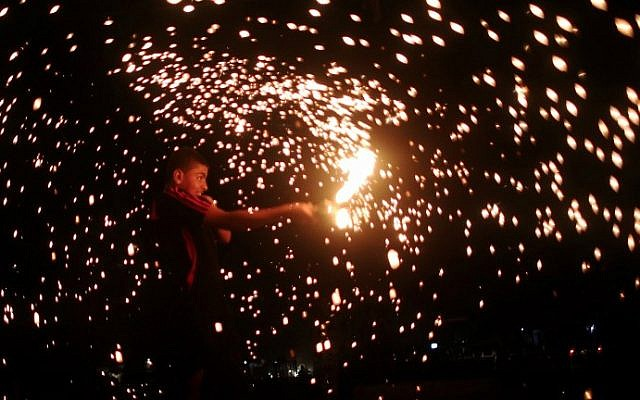 A Palestinian boy celebrates with fireworks during the Muslim holy month of Ramadan, in Rafah, in the southern Gaza Strip, as the faithful prepare for the start of the Muslim holy month, on June 17, 2015. (AFP PHOTO/SAID KHATIB)