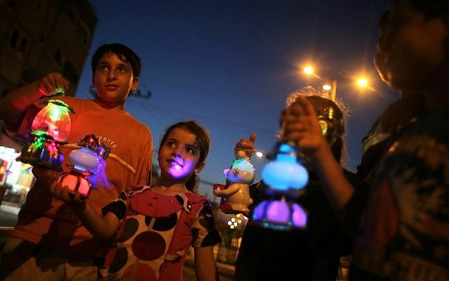 """Palestinian children hold traditional lanterns known in Arabic as """"Fanous"""" sold during the Muslim holy month of Ramadan, in Rafah, in the southern Gaza Strip, as the faithful prepare for the start of the Muslim holy month, on June 17, 2015. (AFP PHOTO/SAID KHATIB)"""