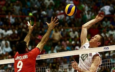 US player David Smith (R) smashes past Iran's Adel Gholami (L) during the volleyball World League pool B match between Iran and USA at Tehran's Azadi arena on June 19, 2015, in which Iran won 3-0 (Behrouz Mehri/AF)