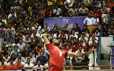 Iran's Adel Gholami serves the ball as a few women sit amid the fans during the volleyball World League pool B match between Iran and USA at Tehran's Azadi arena on June 19, 2015, in which Iran won 3-0 (AFP PHOTO / BEHROUZ MEHRI)
