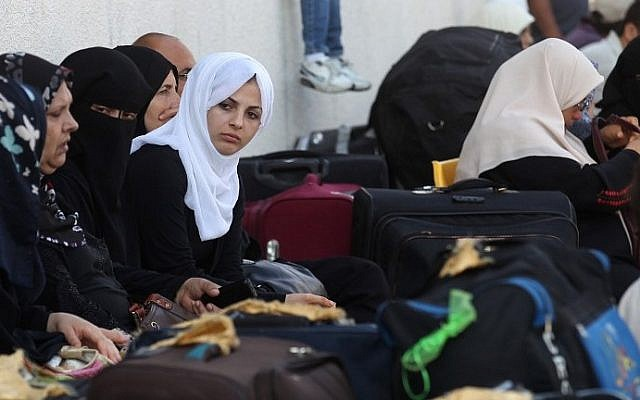 Palestinian women wait with their luggage to cross into Egypt at the Rafah Border Crossing in the southern Gaza Strip on June 23, 2015. (Said Khatib/AFP)
