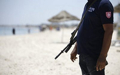 A Tunisian policeman patrols the beach in front of the Riu Imperial Marhaba Hotel in Port el Kantaoui, on the outskirts of Sousse  on June 28, 2015, following a shooting attack two days earlier. (AFP PHOTO / KENZO TRIBOUILLARD)