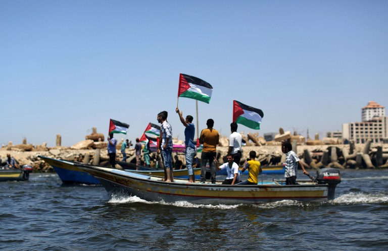 Palestinians wave flags as they ride boats in support of activists aboard a flotilla made up of four boats aimed at defying Israel's blockade of Gaza, at the seaport of Gaza City on June 28, 2015. (Mahmud Hams/AFP)