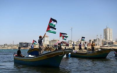 Palestinians wave flags as they ride boats in the seaport of Gaza City on June 28, 2015. (Mahmud Hams/AFP)