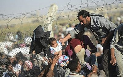 Syrians fleeing the civil war pass through broken border fences and trenches to enter Turkish territory illegally, near the Turkish border crossing at Akcakale in Sanliurfa province on June 14, 2015. (AFP/BULENT KILIC)
