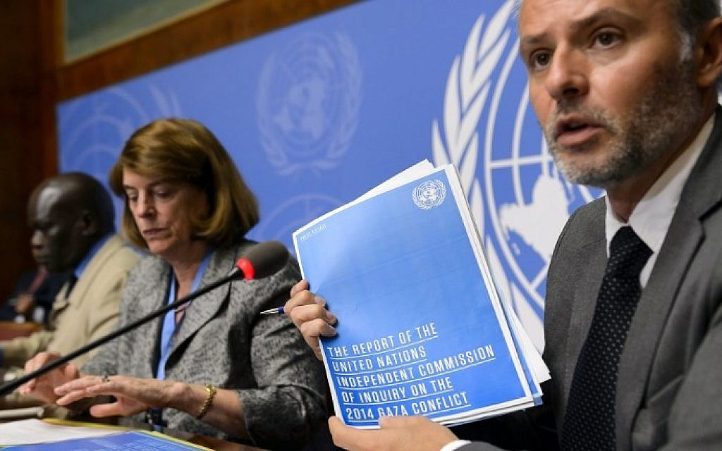 Information Officer for the Office of the High Commissioner for Human Rights Rolando Gomez holds the report of the Commission of Inquiry on the 2014 Gaza conflict next to Commission chairperson Mary McGowan Davis, center, and Commission member Doudou Diene during a press conference on their report on June 22, 2015 at the United Nations Office in Geneva. (AFP / FABRICE COFFRINI)