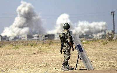 A picture taken from the Turkish side of the border with Syria shows a Turkish soldier watching as smoke rises from the Syrian town of Kobani, on June 27, 2015. (Bulent Kilic/AFP)