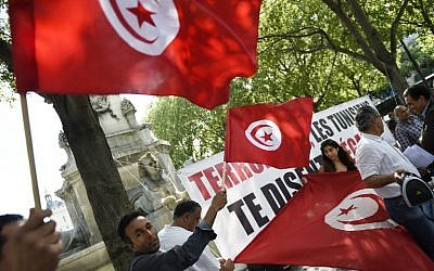 Protesters wave Tunisian flags during a demonstration against terrorism in Paris on June 27, 2015, a day after a deadly attack on a Tunisian beach resort. (AFP/LOIC VENANCE)