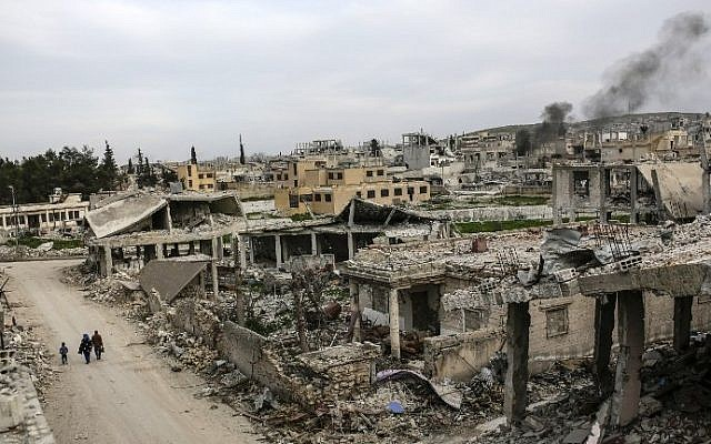People walking along a conflict damaged street in the Syrian town of Kobane, March 27, 2015.  Islamic State group fighters reentered the battleground town on June 25, 2015. (AFP/YASIN AKGUL)