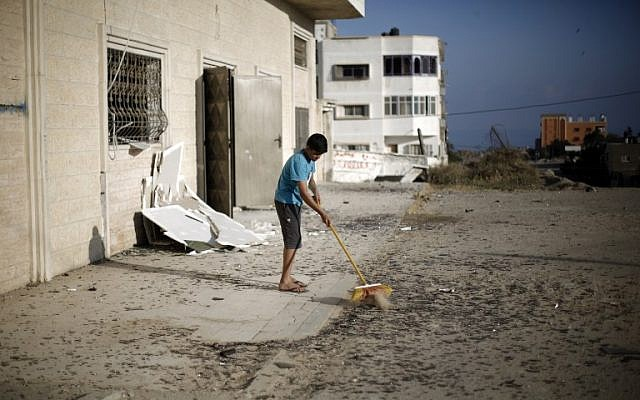 A Palestinian boy cleans debris near a training base of the Ezzedine al-Qassam brigades, the military wing of Hamas, in Gaza City, after Israeli warplanes struck multiple targets on June 4, 2015, in response to Palestinian rocket fire. (AFP/MOHAMMED ABED)
