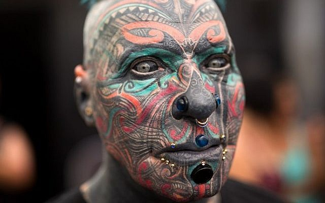 A man whose face is completely covered with tattoos poses during the three-day annual tattoo festival on June 6, 2015 in the coastal city of Tel Aviv (Menahem Kahana/AFP)