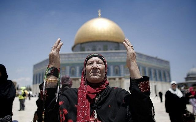 Palestinian Muslim worshipers pray outside the Dome of the Rock at the Al-Aqsa Mosque compound in Jerusalem during the first Friday prayer of the holy month of Ramadan, on June 19, 2015. (AFP/AHMAD GHARABLI)