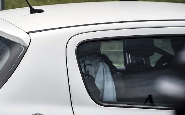 A suspect (head covered) in the attack on the Air Products gas factory is taken away in a car of the French criminal investigation police after a search at the suspect's home in the Moines neighborhood of Saint-Quentin-Fallavier, near Lyon, central eastern France, on June 26, 2015. (AFP/JEAN-PHILIPPE KSIAZEK)