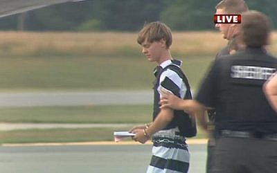 In this screen grab taken from WBTV News, shooting suspect Dylann Roof (L) is escorted by police at the Shelby-Cleveland County Regional Airport for extradition back to Charleston, South Carolina in Shelby, North Carolina on June 18, 2015. (AFP/ WBTV NEWS/ HO)