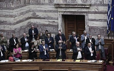 Greek Prime Minister Alexis Tsipras (R) acknowledges applause from his party's lawmakers during a parliamentary session in Athens on June 28, 2015 (AFP PHOTO / ANGELOS TZORTZINIS)