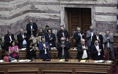 Greek Prime Minister Alexis Tsipras (R) acknowledges applause from his party's lawmakers during a parliamentary session in Athens on June 28, 2015. Greece will hold a referendum on July 5 on the outcome of negotiations with its international creditors taking place in Brussels. (Angelos Tzortzinis/AFP)