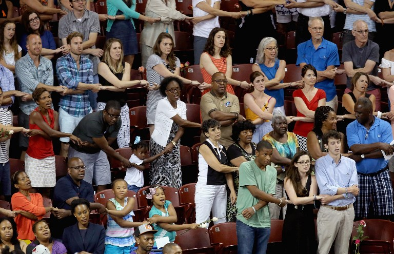 Thousands of people hold hands and sing 'We Shall Overcome' during a prayer vigil for the nine victims of the Emanuel AME Church shooting at the College of Charleston TD Arena June 19, 2015 in Charleston, South Carolina (Chip Somodevilla/Getty Images/AFP)