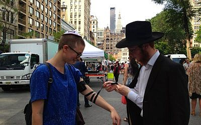 A Chabad representative lays tefillin on Baci Weiler in New York's Union Square on Friday, June 19, 2015 (Facebook)