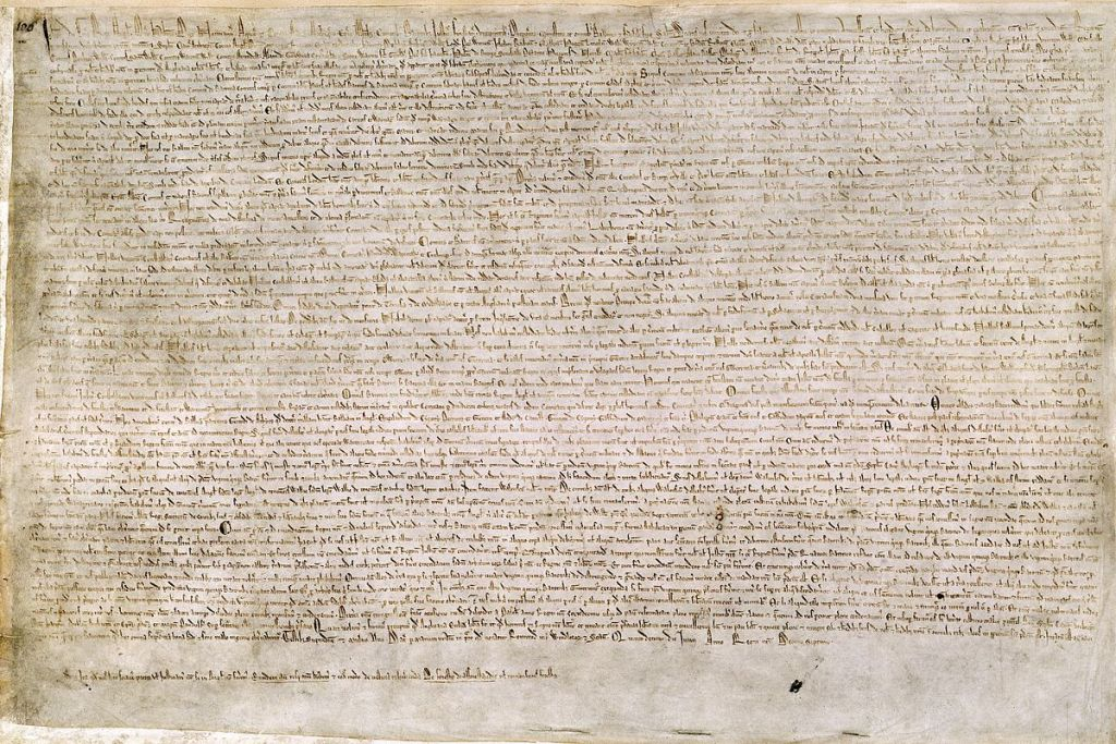 The Magna Carta (originally known as the Charter of Liberties) of 1215, written in iron gall ink on parchment in medieval Latin, using standard abbreviations of the period, authenticated with the Great Seal of King John. (Public Domain via wikipedia; British Library)