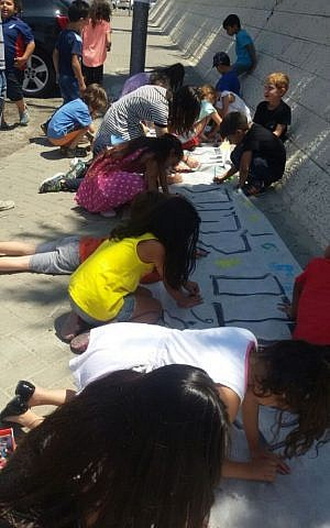 Students and teachers create signs on June 30, 2015 to cover the racist graffiti spray painted on their school's walls the night before. (Courtesy: Hand in Hand)