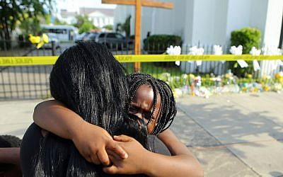 Kearston Farr hugs her 5-year-old daughter Taliyah visiting a memorial in front of the Emanuel AME Church on Friday, June 19, 2015 in Charleston, S.C.  (Curtis Compton/Atlanta Journal-Constitution via AP)