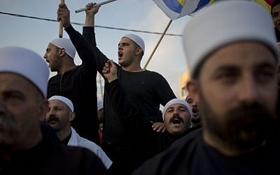 Members of Israel's Druze minority shout slogans and wave their flags during a march in the Druze village of Yarka, Israel, Sunday, June 14, 2015 (AP/Ariel Schalit)