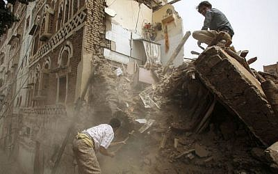 A man searches for survivors under the rubble of houses destroyed by Saudi airstrikes in the old city of Sana'a, Yemen, June 12, 2015. (AP/Hani Mohammed)