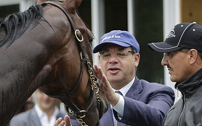 Ahmed Zayat, left, owner of Kentucky Derby and Preakness Stakes winner American Pharoah, approaches the horse as he is held for a bath by hot walker Juan Ramirez after a workout at Belmont Park, Friday, June 5, 2015, in Elmont, New York (AP Photo/Julie Jacobson)