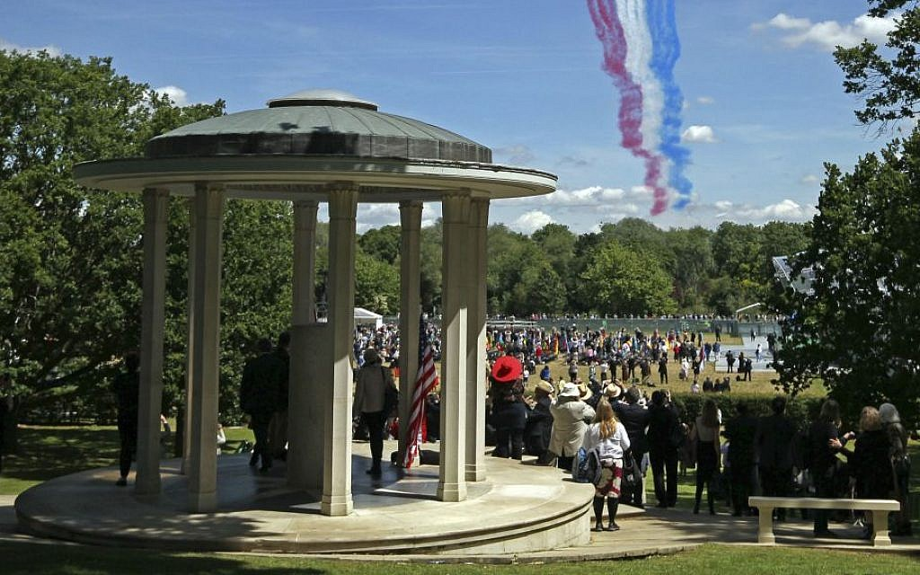 People gather at the riverside meadow west of London as the Red Arrows RAF display team fly over the Magna Carta memorial in Runnymede, England, during a commemoration ceremony Monday June 15, 2015, to celebrate the 800th anniversary of the groundbreaking accord called Magna Carta. (Steve Parsons / Pool photo via AP)