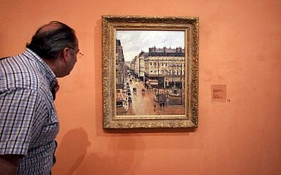 An unidentified visitor looks at the Impressionist painting called 'Rue St.-Honore, Apres-Midi, Effet de Pluie,' painted in 1897 by Camille Pissarro, on display in the Thyssen-Bornemisza Museum in Madrid, May 12, 2005 (AP Photo/ Mariana Eliano, File)