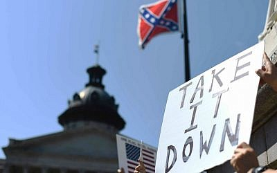 Protesters hold a sign during a rally to take down the Confederate flag at the South Carolina Statehouse, Tuesday, June 23, 2015, in Columbia, South Carolina. (AP Photo/Rainier Ehrhardt)