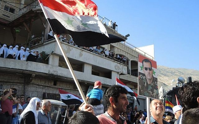 A man holds a Syrian flag and a poster of President Bashar Al Assad during a pro-Syrian army protest in Majdal Shams on Monday. (Melanie Lidman/Times of Israel)