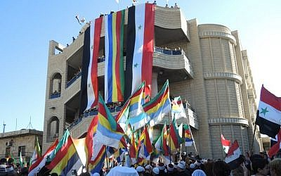 Syrian and Druze flags at a pro-Assad protest in the Druze village of Majdal Shams in the Golan Heights on Monday. (Melanie Lidman/Times of Israel)