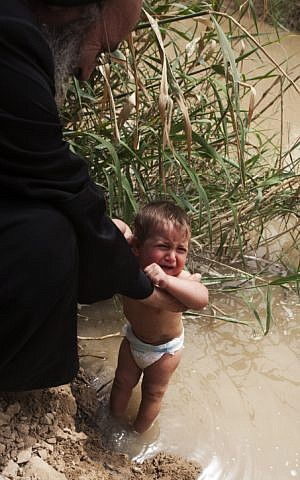A child is baptized on Orthodox Easter at the Qasr-al-Yahud site on April 14, 2009. (Matanya Tausig/Flash 90)