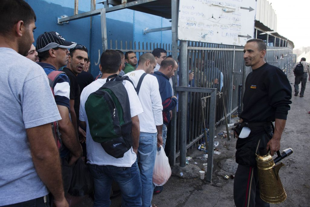 Palestinian workers wait to cross through a checkpoint in Bethlehem, June 2, 2013 (Neal Badache/FLASH90)
