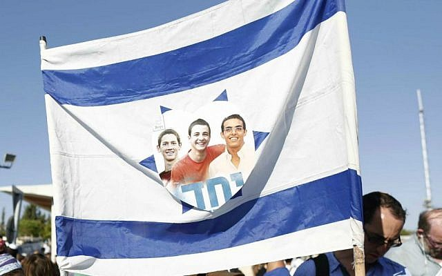 Israeli flag with the picture of the three murdered teens and the Hebrew word 'yachad' (united) seen at their joint funeral ceremony, in the Modiin cemetery, on July 1, 2014. (Yonatan Sindel/Flash90)