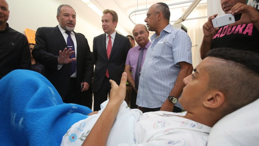 With Norwegian Foreign Minister Boerge Brende, foreign minister Avigdor Liberman visits a boy who was wounded in a rocket attack from Gaza, July 16, 2014. (Photo by Yossi Zamir/Flash90)