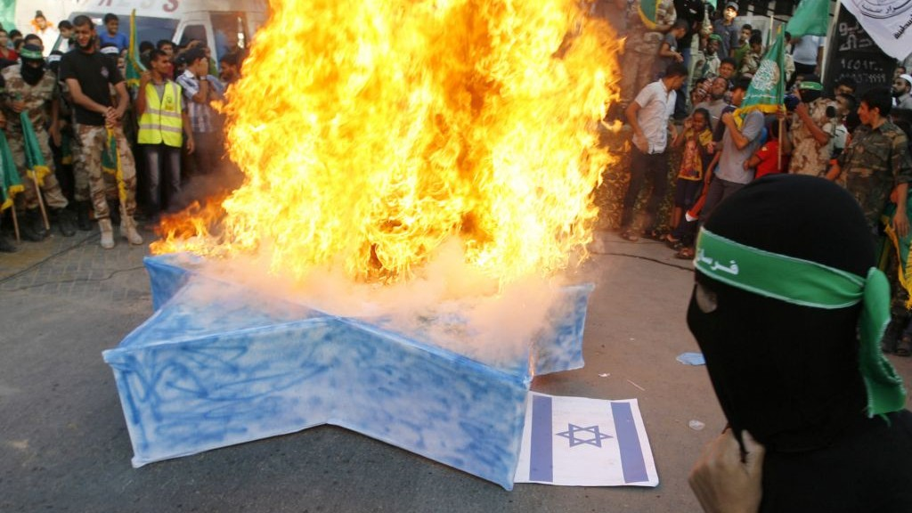 Masked Hamas members burn a cut-out of a Star of David during a demonstration in Rafah in the southern Gaza Strip, August 17, 2014. (Photo by Abed Rahim Khatib/Flash90)